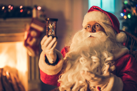 Happy Santa Claus in eyeglasses is preparing to Christmas in his residence, sitting in rocking chair with  hourglass. Last minutes before the New Year coming. Stock Photo