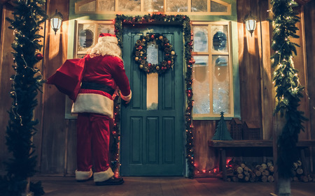 Santa Claus is bringing gifts for Christmas. Standing on the decorated porch with bag of presents, opening the door and going in house.