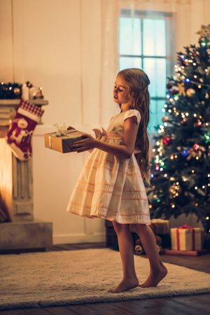 Little cute girl in dress is waiting for Christmas at home. Charming kid in New Year Eve with gift box in hands. Banque d'images