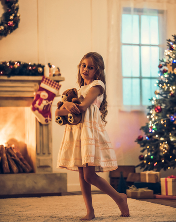Little cute girl in dress is waiting for Christmas at home. Charming kid with teddy bear in hands in New Year Eve. 版權商用圖片