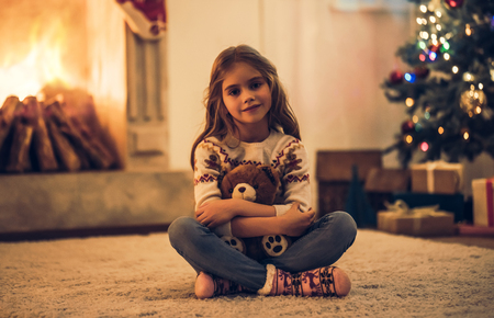 Little cute girl is waiting for Christmas at home. Charming kid with teddy bear in hands in New Year Eve. Stock Photo