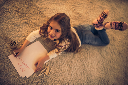 Little cute girl is waiting for Christmas at home. Top view of charming kid is writing letter to Santa Claus in New Year Eve. Archivio Fotografico