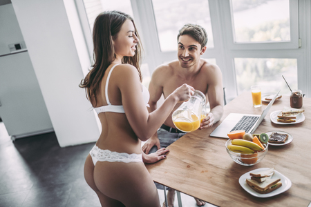 Good morning! Young romantic couple is having breakfast on modern light kitchen. Handsome man is sitting at the table with laptop while his sexy woman is standing nearby in underwear with orange juice. Healthy lifestyle concept.