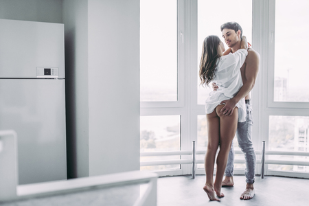 Good morning! Young romantic couple on light modern kitchen with panoramic windows. Sexy young woman in underwear and shirtless handsome man are spending time together. Passionate lovers. 写真素材