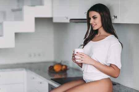 Good morning! Young woman in underwear is sitting on light modern kitchen with cup of coffee in hands and smiling.