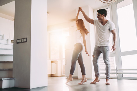 Romantic couple at home. Attractive young woman and handsome man are enjoying spending time together. Passionate couple is dancing on light modern kitchen with paniramic windows. Фото со стока