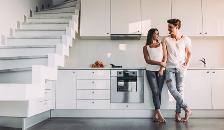 Full-length image of romantic couple at home. Attractive young woman and handsome man are enjoying spending time together while standing on light modern kitchen.