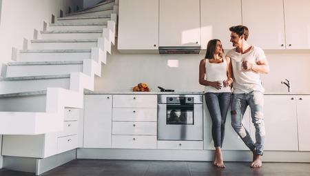 Imagen de cuerpo entero de pareja romántica en casa. La mujer joven atractiva y el hombre hermoso gozan el pasar de tiempo juntos mientras que se coloca en la cocina moderna ligera con la taza de café en manos.