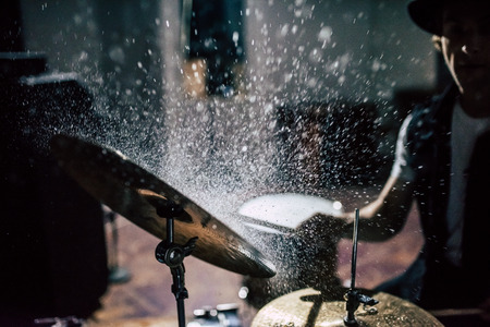 Repetition of rock music band. Cropped image of drummer behind the drum set. Water splashes on cymbal. 版權商用圖片