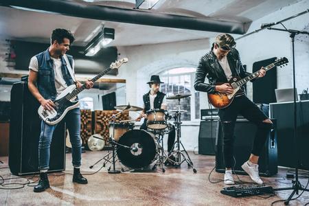 Répétition de groupe de musique rock. Bassiste, guitariste électro et batteur derrière le set de batterie. Base de répétition