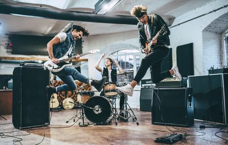 Herhaling van rockband. Basgitarist, electro gitarist en drummer achter het drumstel. Repetitiebasis