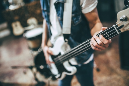 Repetition of rock music band. Cropped image of bass guitar player. Rehearsal base Stock Photo
