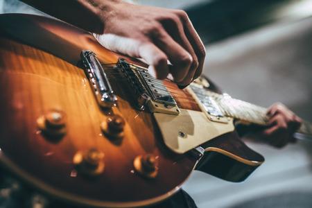 Powtórzenie zespołu rockowego. Przycięty obraz gitarzysty elektro. Baza prób