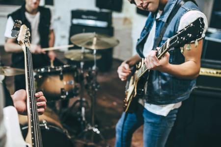 Répétition d'un groupe de musique rock. Image recadrée du bassiste, du guitariste électro et du batteur derrière la batterie. Base de répétition Banque d'images - 90779082