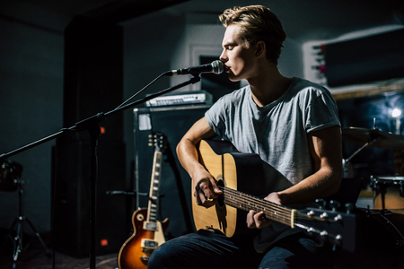 Handsome young man on rehearsal base. Lyric singer with acoustic guitar. Stock Photo