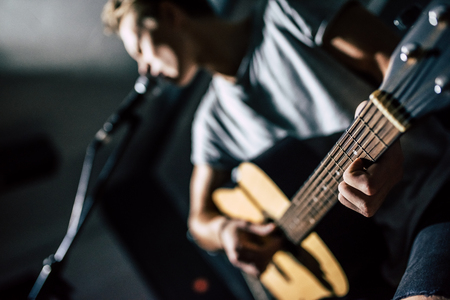Cropped image of handsome young man on rehearsal base. Lyric singer with acoustic guitar. Stock Photo