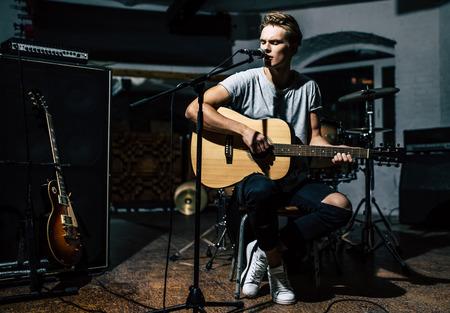 리허설 기지에서 잘 생긴 젊은 남자. 서정 기타와 가사 가수.