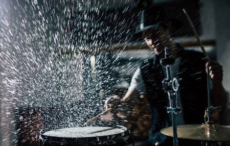 Repetition of rock music band. Drummer behind the drum set. Water splashes on snare drum. 版權商用圖片