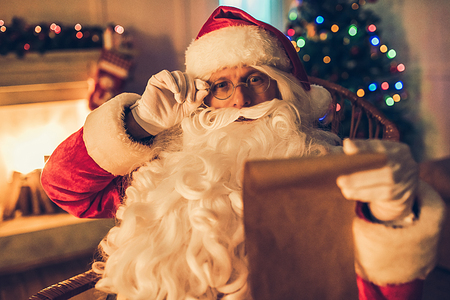 Surprised Santa Claus in eyeglasses is preparing to Christmas in his residence, sitting in rocking chair and reading big wish list.