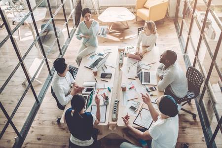 Widok z góry wielorasowych młodych kreatywnych ludzi w nowoczesnym biurze.
