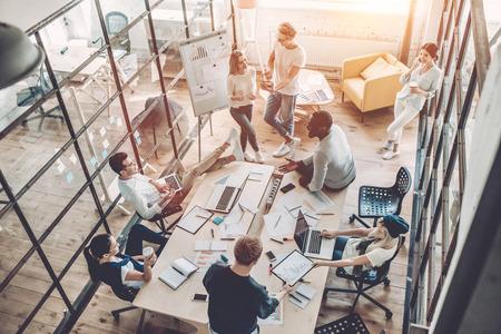 Draufsicht von den gemischtrassigen jungen kreativen Leuten im modernen Büro. Gruppe junge Geschäftsleute arbeiten zusammen mit Laptop, Tablette, intelligentem Telefon, Notizbuch. Erfolgreiche Hipster-Team in Coworking. Freiberufler.