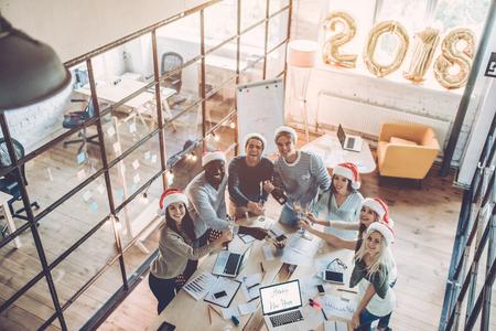 기쁜 성탄과 새해 복 많이 받으러! multiracial 젊은 창조적 인 사람들의 상위 뷰는 현대 사무실에서 휴가를 축 하합니다.