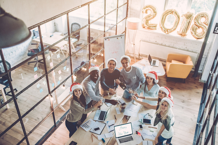 Merry Christmas and Happy New Year 2018! Top view of multiracial young creative people are celebrating holiday in modern office.