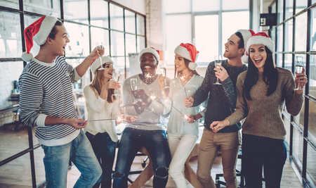 Merry Christmas and Happy New Year 2018!Multiracial young creative people are celebrating holiday in modern office. Stockfoto