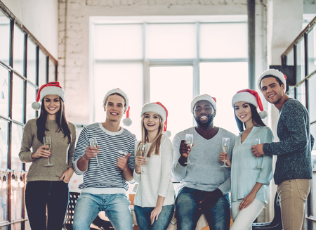 Merry Christmas and Happy New Year 2018!Multiracial young creative people are celebrating holiday in modern office. Standard-Bild