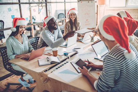 Merry Christmas and Happy New Year 2018!Multiracial young creative people are celebrating holiday in modern office. Stock Photo