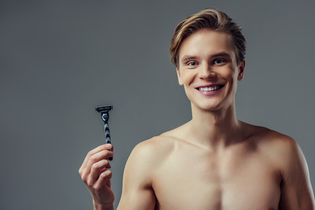 Handsome young man isolated. Portrait of shirtless muscular man is standing on grey background with razor in hand and smiling. Men care concept.