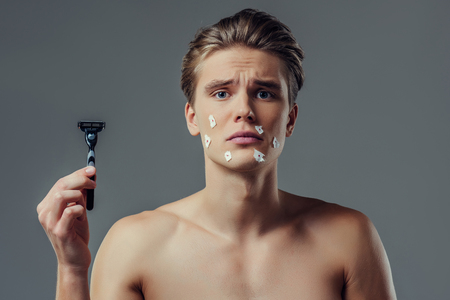 Handsome young man isolated. Portrait of shirtless muscular man is standing on grey background with razor in hand. Men care concept. Get hurt while shaving. 版權商用圖片