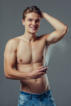 Handsome young man isolated. Portrait of shirtless muscular man is standing on grey background and using deodorant. Men care concept. 版權商用圖片