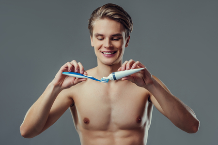 Handsome young man isolated. Portrait of shirtless muscular man is standing on grey background with toothbrush and toothpaste in hand. Men care concept.