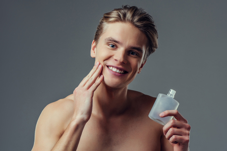 Handsome young man isolated. Portrait of shirtless muscular man is standing on grey background and using face aftershave lotion. Men care concept. 版權商用圖片