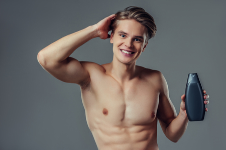 Handsome young man isolated. Portrait of shirtless muscular man is standing on grey background with shampoo in hand. Men care concept. 版權商用圖片