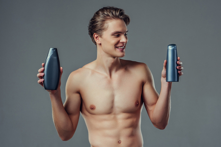 Handsome young man isolated. Portrait of shirtless muscular man is standing on grey background with shampoo in hands. Men care concept.