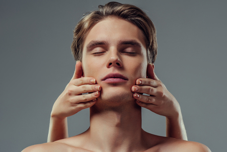 Handsome young man isolated. Portrait of shirtless muscular man is standing on grey background. Close-up of mens face while making face massage. Men care concept.