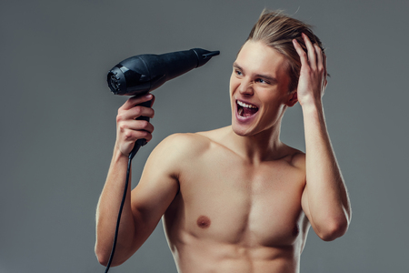Handsome young man isolated. Portrait of shirtless muscular man is standing on grey background with hair dryer in hand. Men care concept.