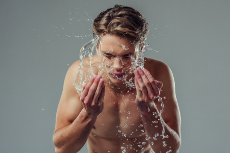 Handsome young man isolated. Portrait of shirtless muscular man is standing on grey background and washing oneself. Spraying water into face. Men care concept.