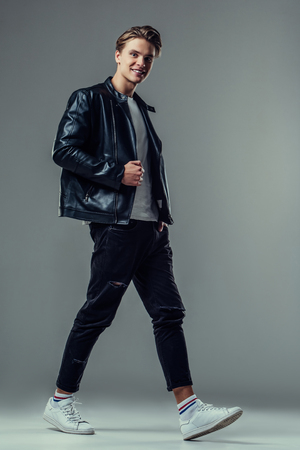 Handsome young man isolated. Fashionable  man in leather jacket is walking on grey background. 版權商用圖片