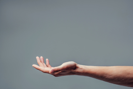 Man hand isolated on grey background. Holding something from below. Asking for help gesture.