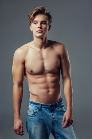 Handsome young man isolated. Shirtless muscular man in jeans is standing on grey background.