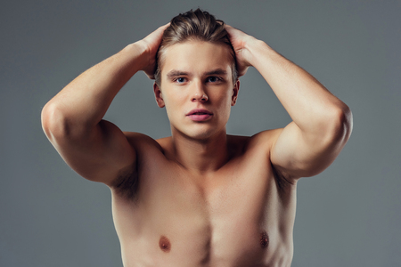 Handsome young man isolated. Portrait of shirtless muscular man is standing on grey background. Serious man looking at camera.