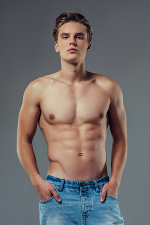 Handsome young man isolated. Shirtless muscular man in jeans is standing on grey background. Serious man looking at camera.