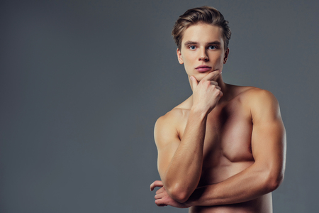 Handsome young man isolated. Portrait of shirtless muscular man is standing on grey background.