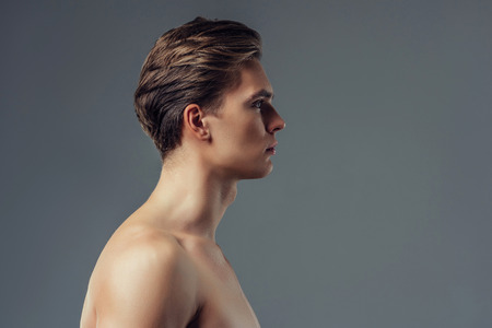 Handsome young man isolated. Portrait of shirtless muscular man is standing on grey background turned in profile.
