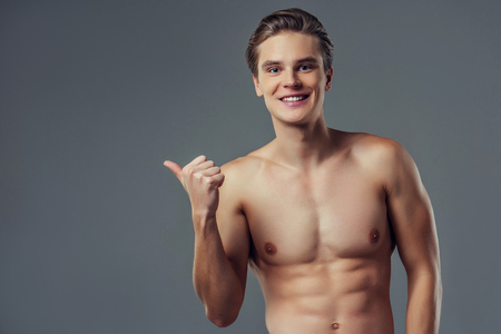 Handsome young man isolated. Portrait of shirtless muscular man is standing on grey background and pointing to the side. Showing product.