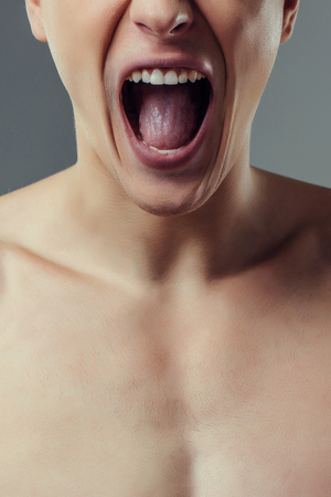 Handsome young man isolated. Cropped image of shirtless muscular man is standing on grey background and shouting. Close-up of men face.