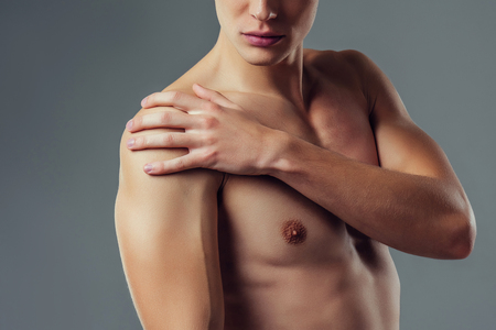Handsome young man isolated. Cropped image of shirtless muscular man is standing on grey background. Close-up of man holding his shoulder. Experiencing shoulder pain. 版權商用圖片